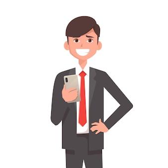 Szczęśliwy uśmiechnięty biznesmen trzyma w ręku smartfona