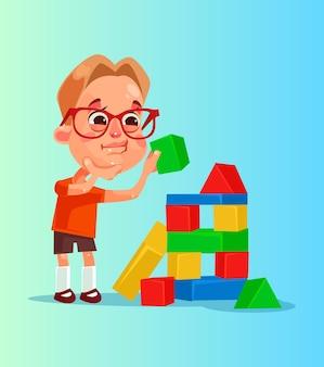Szczęśliwy uśmiechnięty chłopiec buduje piramidę z kostek