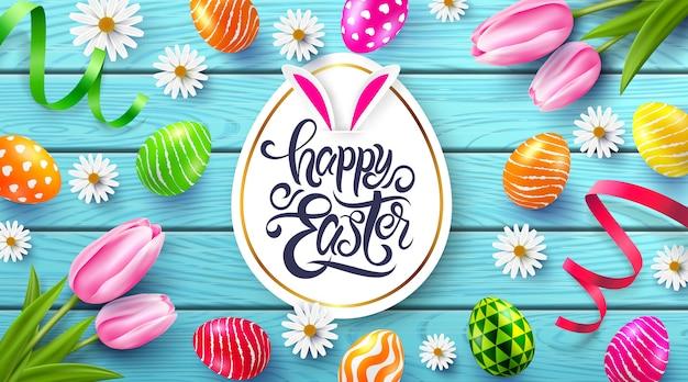Szczęśliwy wielkanocny plakat i szablon z kolorowymi wielkanocnymi jajkami i kwiatem na drewno stole.