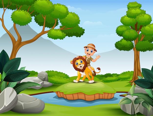Szczęśliwy zookeeper chłopiec i lew bawić się w naturze