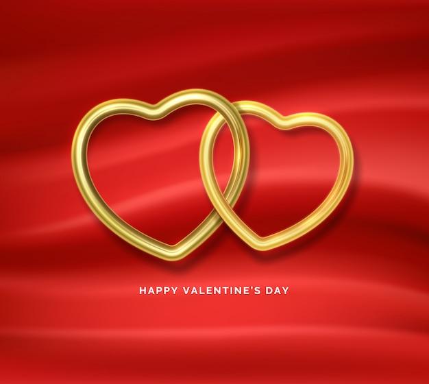 Szczęśliwych walentynek. dwa złote kształty serca połączone ze sobą na czerwonej jedwabnej tkaninie.