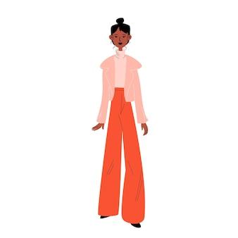 Szczupła młoda kobieta w szerokich czerwonych dżinsach i różowej skórzanej kurtce.