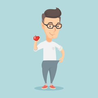 Szczupły mężczyzna w spodniach pokazujący wyniki swojej diety.