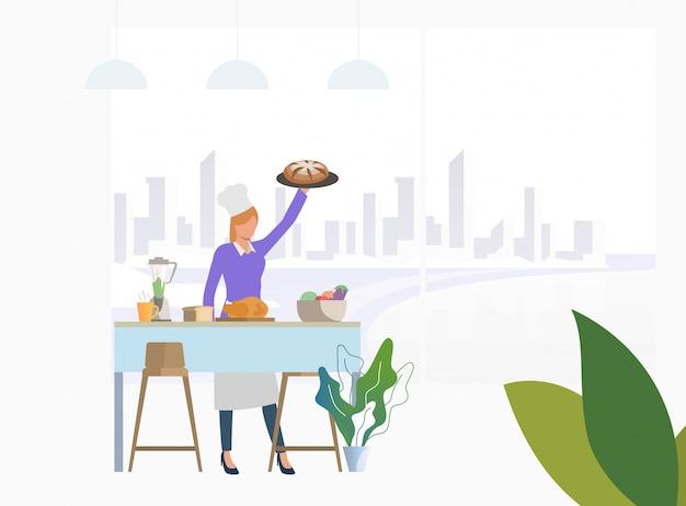 Szef kuchni gotuje obiad przy kuchennym stołem i trzyma kulebiaka
