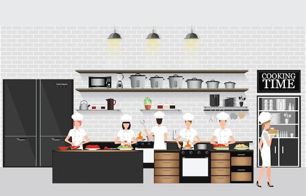 Szefowie kuchni gotuje przy stołem w restauracyjnym kuchennym wnętrzu