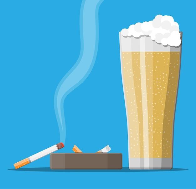 Szklanka piwa z papierosem i popielniczką. alkohol, tytoń. piwo alkoholowe, produkty do palenia. koncepcja niezdrowego stylu życia.