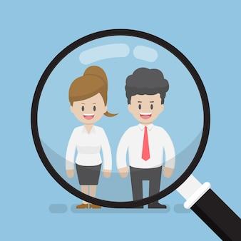 Szkło powiększające koncentruje się na biznesmenie i bizneswoman. koncepcja rekrutacji zasobów ludzkich.
