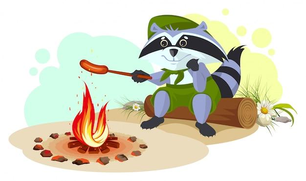 Szop pracz smaży kiełbaski w ogniu