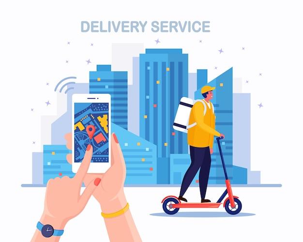 Szybka dostawa hulajnogą. kurier dostarcza jedzenie na zamówienie. telefon z aplikacją mobilną