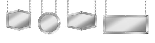 Szyldy metalowe o różnych kształtach, tablica ze stalową ramą zawieszona na łańcuchach.