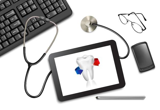 Tabliczka dotykowa tabletu i materiały biurowe na stole u lekarza.