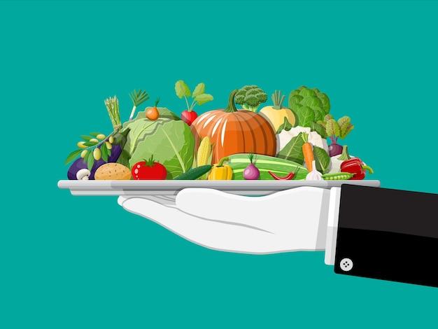 Taca pełna warzyw w dłoni.