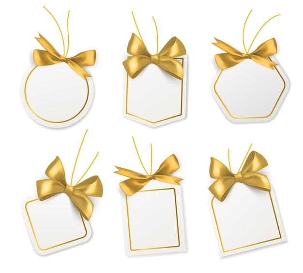 Tagi ze złotymi kokardkami. puste białe etykiety papierowe ze złotymi satynowymi lub jedwabnymi wstążkami na boże narodzenie, urodziny lub wesele opakowanie prezent wektor realistyczne izolowane szablony kolekcji