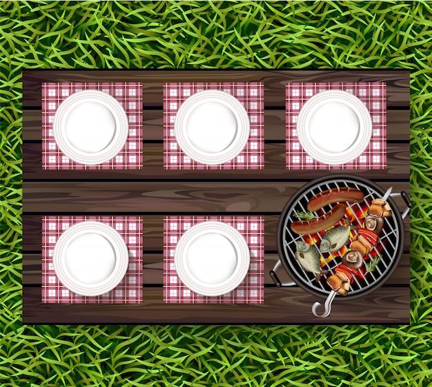 Talerze na zielonej trawie i kiełbasy na grillu