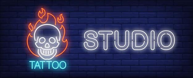 Tatuaż studio neon znak. uśmiechnięty scull na pożarniczej i dużej inskrypci na ciemnym ściana z cegieł.
