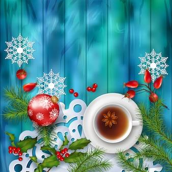 Tea party tło z filiżanką herbaty i ozdób choinkowych na drewnianym stole