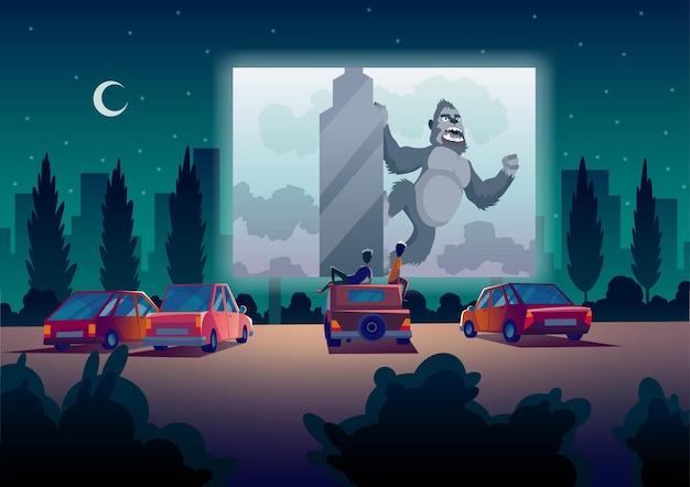 Teatr drivein z samochodami stoi na parkingu na świeżym powietrzu w nocy