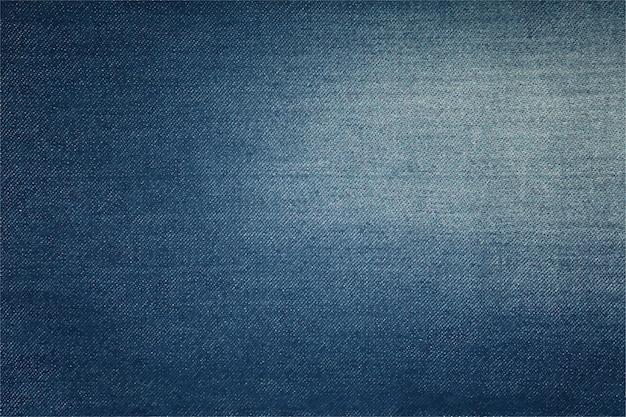 Tekstura tła dżinsów bawełnianych w kolorze ciemnego indygo z lekko spranym, wyblakłym obszarem