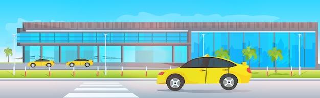 Terminal lotniska przed żółtymi taksówkami w pobliżu poziomych odlotów nowoczesnych samolotów
