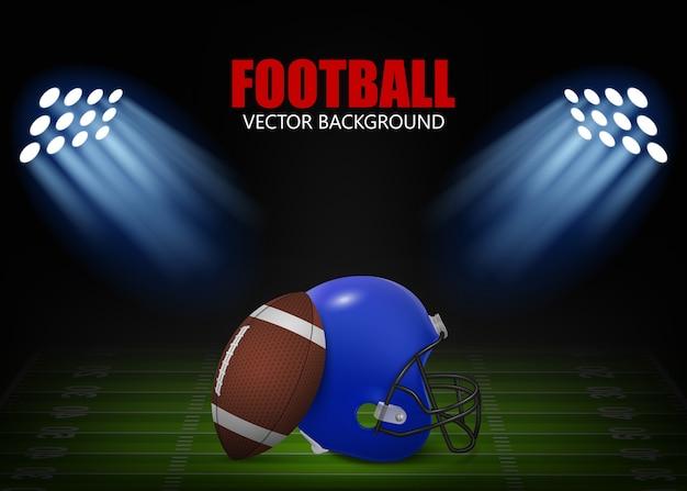 Tło futbolu amerykańskiego - kask i piłka na boisku oświetlone reflektorami.