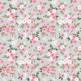 Tło kwiatowy. wzór z małych różowych kwiatów na szarym tle.