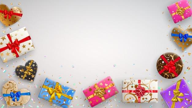 Tło z kolorowymi pudełkami prezentowymi ze wstążkami, kokardkami i różnymi wzorami