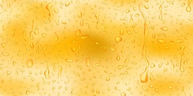 Tło z kroplami i smugami wody w żółtych kolorach, spływającej po powierzchni