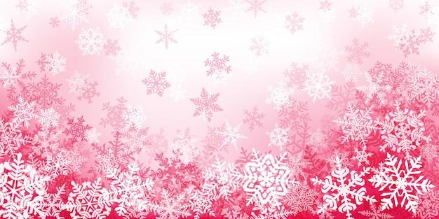 Tło złożonych świątecznych płatków śniegu w kolorach czerwonym i różowym. zimowa ilustracja z padającym śniegiem