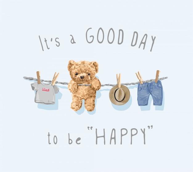 To dobry dzień, bądź szczęśliwy, slogan z zabawką słodkiego misia i ubraniami wiszącymi na ilustracji liny