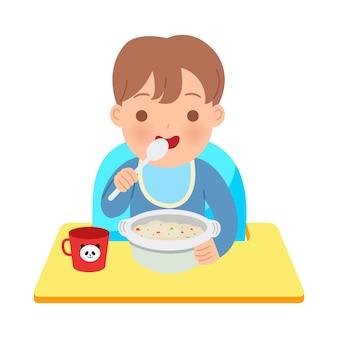 Toddler chłopiec siedzi na krzesełku dziecka, je miskę owsianki. szczęśliwa ilustracja rodzicielstwa. światowy dzień dziecka. na białym tle.