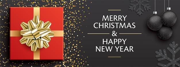 Transparent świąteczne pozdrowienia z czerwonym pudełkiem, złotą wstążką, bombkami choinkowymi i płatkami śniegu