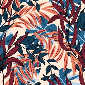Trendu abstrakcjonistyczny bezszwowy wzór z kolorowymi tropikalnymi liśćmi i roślinami na beżowym tle
