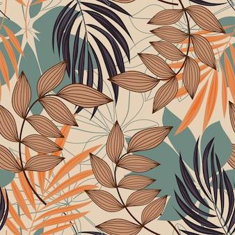 Trendu abstrakcjonistyczny bezszwowy wzór z kolorowymi tropikalnymi liśćmi i roślinami na beżu