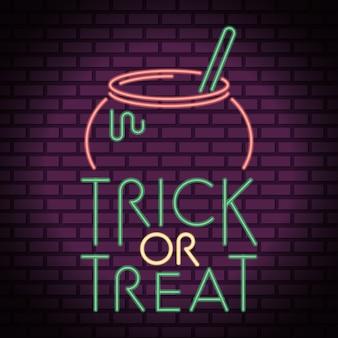 Trick or treat halloween napis w świetle neonu z kociołkiem