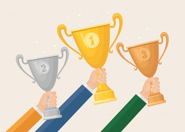 Trofeum w dłoni. złoty, srebrny, brązowy kielich na białym tle na tle. nagrody dla zwycięzcy, mistrza. koncepcja zwycięstwa, nagrody, mistrzostwa, przywództwa, osiągnięcia. płaska konstrukcja