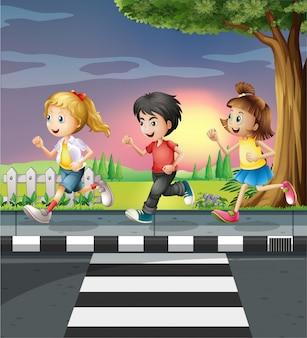 Troje dzieci biegających wzdłuż drogi