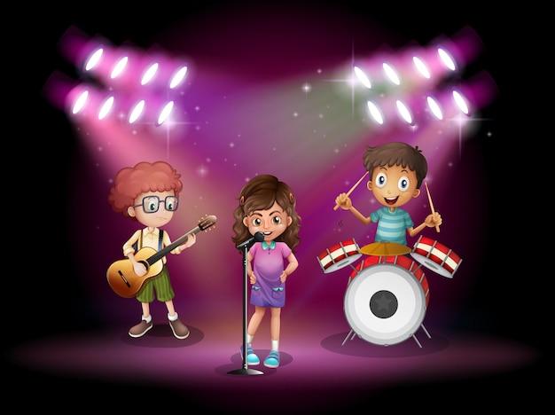 Troje dzieci grających muzykę na scenie
