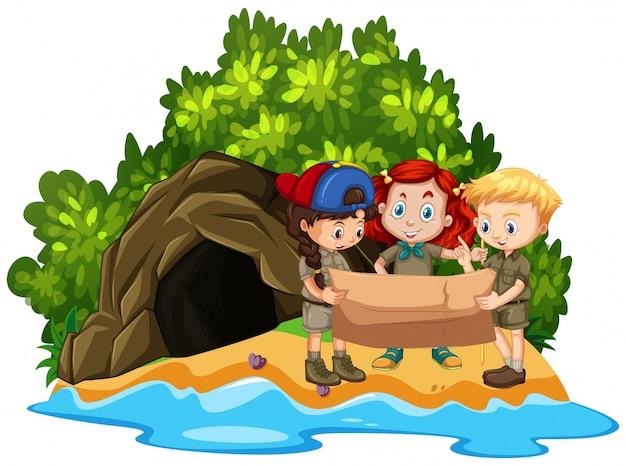 Troje dzieci patrząc na mapę przed jaskinią na wyspie
