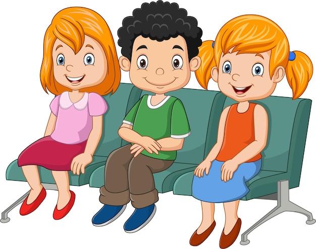 Troje małych dzieci siedzi na siedzeniu