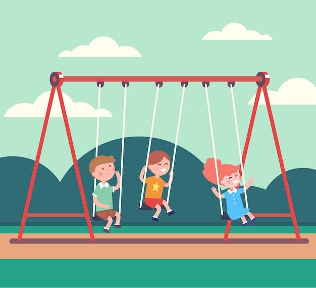 Trzy dzieci chłopców i dziewczynka huśtawka w parku publicznym