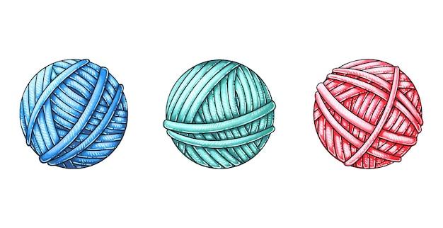 Trzy kulki wełny na drutach.