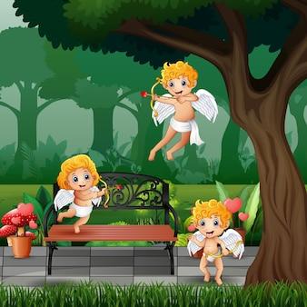 Trzy małe amorki na ilustracji parku