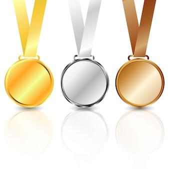 Trzy metalowe medaliony: złote, srebrne i brązowe.