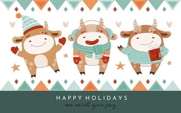 Trzy słodkie byki w zimowe ubrania. kartka świąteczna z wizerunkiem byków kreskówek.