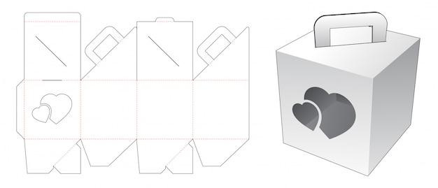 Trzymający karton z szablonem wycinanym w oknie serca