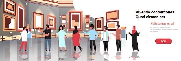 Turyści w galerii sztuki współczesnej muzeum wnętrze wyglądające kreatywne obrazy współczesne dzieła sztuki lub eksponaty spotkanie gości