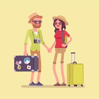 Turyści w stroju podróżnym z bagażem i walizkami