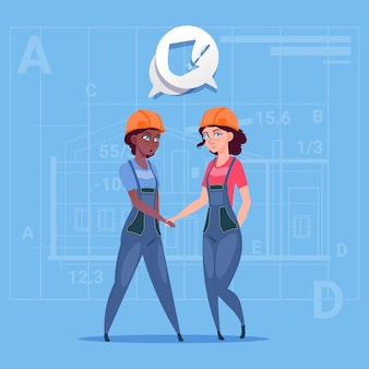 Two mix race female builders shaking hands