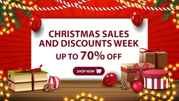 Tydzień świątecznych wyprzedaży i rabatów, czerwony sztandar z białą kartką papieru, świąteczne książki i prezenty na drewnianym stole