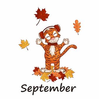 Tygrys jest symbolem chińskiego nowego roku, z napisem september. w ciepłym kapeluszu z opadającymi jesiennymi liśćmi. idealny do tworzenia kalendarza. wektor ilustracja stylu cartoon